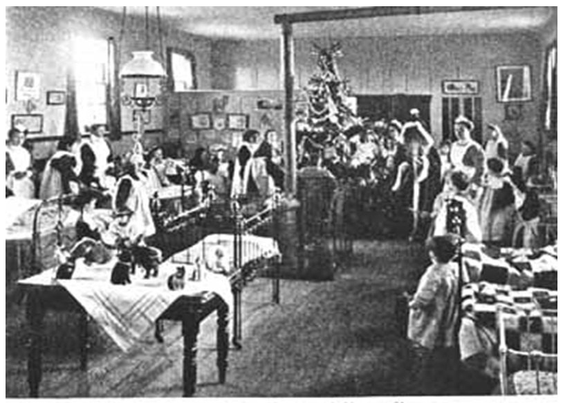 The dormitory at the Byfleet Home during Christmastide, c. 1908. Taken from Our Waifs and Strays, February 1908, p. 271. Reproduced from Hidden Lives Revealed